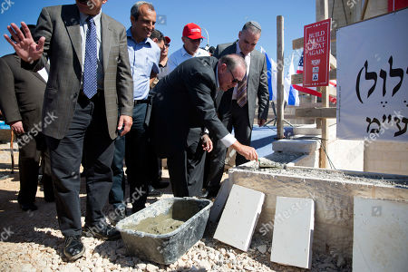 U.S. Governor Mike Huckabee, centre, lays a brick at a new housing complex in the West Bank settlement of Efrat