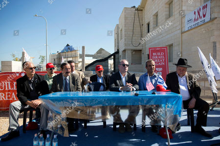 U.S. Governor Mike Huckabee, centre right, listens to a question from the media prior to laying a brick at a new housing complex in the West Bank settlement of Efrat
