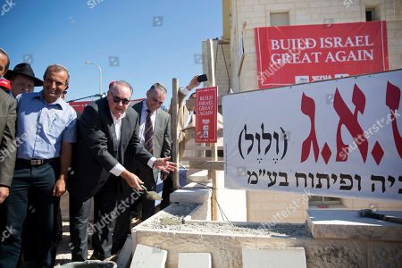U.S. Governor Mike Huckabee, third left, lays a brick at a new housing complex in the West Bank settlement of Efrat