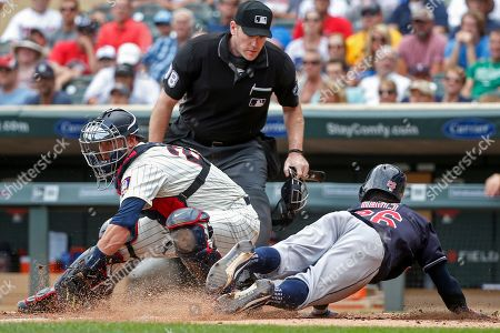 Cleveland Indians Rajai Davis, right, slides ahead of the play by Minnesota Twins catcher Mitch Garver to steal home as umpire Chris Conroy watches in the sixth inning of a baseball game, in Minneapolis