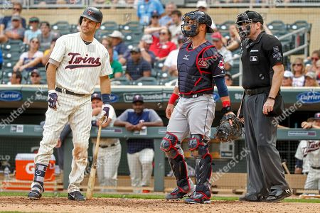 Minnesota Twins' Joe Mauer, left, expresses disappointment in the third strike call by umpire Chris Conroy as Cleveland Indians catcher Yan Gomes awaits the next batter in the ninth inning of a baseball game, in Minneapolis. The Indians won 2-0