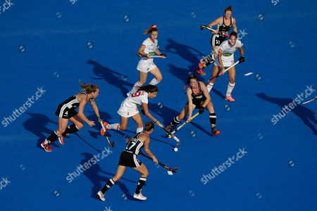 Spain's Lucia Jimenez, center, runs with the ball during the Women's Hockey World Cup quarterfinal match between Germany and Spain at the Lee Valley Hockey and Tennis Centre in London