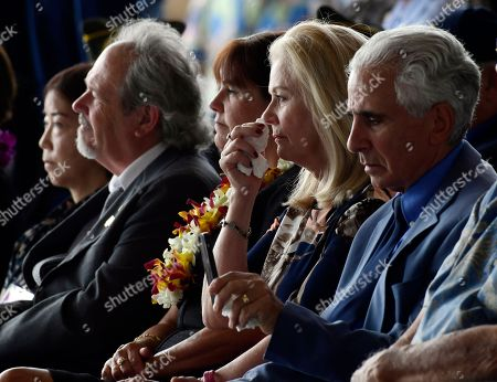 Robert Sanfilkippo, right, sits next to his wife, Diana Brown Sanfilippo who has spent a lifetime searching for her father, 1st Lt. Frank Salazar who died 66 years ago in North Korea, who wipes her eyes as she sits in the audience with Karen Pence, wife of Vice President Mike Pence, at a ceremony marking the arrival of the remains believed to be of American service members who fell in the Korean War at Joint Base Pearl Harbor-Hickam, Hawaii. North Korea handed over the remains last week. Second from left is Rick Downes, who was three when his father went off to the Korean War, and he has been missing ever since