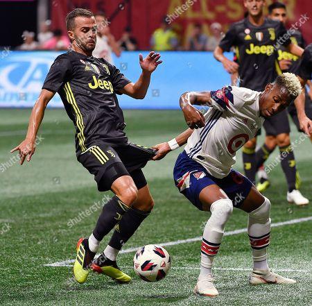 MLS All-Star defender Michael Amir Murillo, right, holds the shorts of Juventus midfielder Miralem Pjanic (5) during the MLS All-Star soccer match, in Atlanta