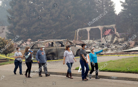 Carol Smith, Tim Smith, Suzie Scalene. Carol Smith, far right in blue, her daughter Suzie Scalene, third from right, and husband Tim, third from left, tour their fire-ravaged neighborhood along with support crews, in Redding, Calif. The Smith's home of 30 years was destroyed by a wildfire
