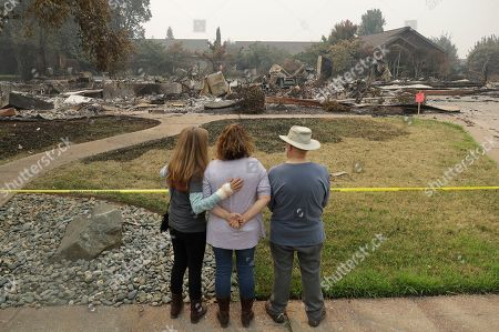 Tim Smith, Suzie Scatena, Deborah Coombs. Tim Smith, at right, gets a first look at his wildfire-ravaged home alongside his daughter, Suzie Scatena, center, and aid worker Deborah Coombs, in Redding, Calif