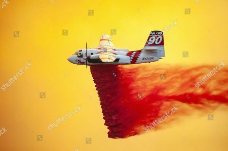 A Cal Fire S-2F3AT drops fire retardant to help stop the spread of the River Fire burning in Lake and Mendocino Counties