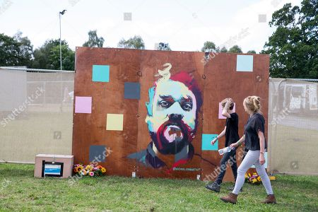Festival-goers walk past a memorial to the late Scott Hutchison, lead singer of Frightened Rabbit