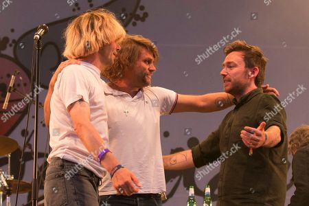 Stock Picture of The Charlatans and Frightened Rabbit embrace after performing a Frightened Rabbit song in tribute to the late Scott Hutchison, lead singer of Frightened Rabbit - Tim Burgess, Grant Hutchison and Billy Kennedy