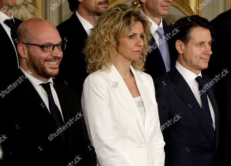 """Made available Friday Aug. 3, 2018 Family Minister Lorenzo Fontana, left, poses with Minister for South Barbara Lezzi, center, and Premier Giuseppe Conte during the swearing -in ceremony for Italy's government at the Quirinale Presidential Palace. Minister Fontana, of the far-right League party, on Friday called for abolishing a 1993 law condemning racist violence, hatred and discrimination, saying """"globalists"""" were using it to """"disguise their anti-Italian racism as anti-Fascism"""