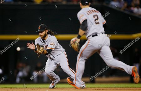 San Francisco Giants shortstop Brandon Crawford, left, fields a grounder hit by Arizona Diamondbacks' Ketel Marte, starting a double play, as second baseman Chase d'Arnaud (2) watches during the seventh inning of a baseball game, in Phoenix. The Diamondbacks won 6-3