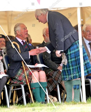 """Prince Charles gets a dram of """"Old Pultney"""" whisky from local hotelier Murray Lamont whilst attending the Mey Highland games"""