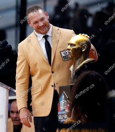 Brett Favre. Former NFL player Brian Urlacher admires his bust before delivering his speech during an induction ceremony at the Pro Football Hall of Fame, in Canton, Ohio