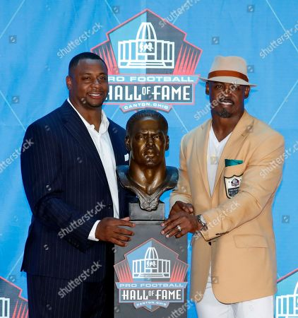 Former NFL player Brian Dawkins, right, poses with a bust of himself and presenter, former teammate Troy Vincent, during an induction ceremony at the Pro Football Hall of Fame, in Canton, Ohio