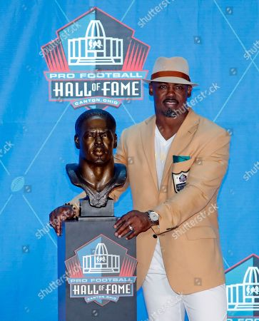 Former NFL player Brian Dawkins poses with a bust of himself during an induction ceremony at the Pro Football Hall of Fame, in Canton, Ohio