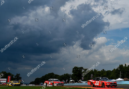 Stock Image of NASCAR Xfinity Series driver Joey Logano (22), driver Ryan Reed (16) and driver Kyle Larson (42) race out of the inner loop as storm clouds move over the track during the NASCAR XFINITY Series Zippo 200 at The Glen on at Watkins Glen International in Watkins Glen, New York