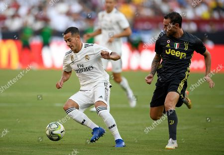 Real Madrid forward Lucas Vázquez, left, dribbles the ball against Juventus midfielder Claudio Marchisio, right, during the second half at an International Champions Cup tournament soccer match, in Landover, Md. Real Madrid won 3-1