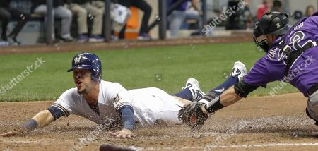 Milwaukee Brewers' Hernan Perez scores past Colorado Rockies catcher Chris Iannetta during the sixth inning of a baseball game, in Milwaukee. Perez scored on a sacrifice fly by Manny Pina