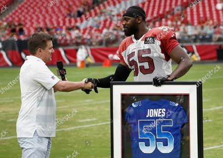 Arizona Cardinals defensive end Chandler Jones (55) shakes hands with team president Michael Bidwill, left, as Jones receives a framed Pro Bowl jersey from the team prior to an NFL football practice, in Glendale, Ariz