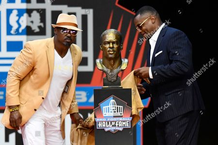 Former NFL safety Brian Dawkins, left, unveils his bust with his presenter, Troy Vincent, during inductions at the Pro Football Hall of Fame, in Canton, Ohio