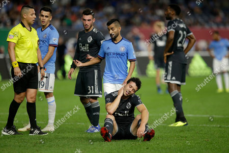 New York City FC's Maximiliano Moralez gestures as Vancouver Whitecaps' Felipe Martins sits on the pitch during the second half of an MLS soccer match, in New York