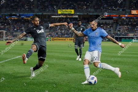 New York City FC's Ronald Matarrita (22) tries to make a cross while defended by Vancouver Whitecaps' Sean Franklin, left, during the second half of an MLS soccer match, in New York