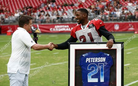 Arizona Cardinals defensive back Patrick Peterson (21) shakes hands with team president Michael Bidwill, left, as Peterson gets his framed Pro Bowl jersey prior to an NFL football practice, in Glendale, Ariz