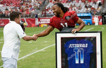 Arizona Cardinals wide receiver Larry Fitzgerald (11) shakes hands with team president Michael Bidwill, left, as Fitzgerald gets his framed Pro Bowl jersey prior to an NFL football practice, in Glendale, Ariz
