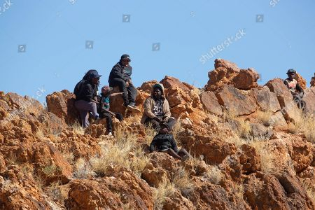 Locals perch above the track on a natural grandstand during the 71st annual Harts Range Races and Rodeo, approximately 215 km East of Alice Springs, Northern Territory, Australia, 04 August 2018 (issued 05 August 2018). Cut out of the bush of Mt. Riddock Station by The Webb brothers, The Harts Range track has been a mainstay of the Central Australian Pastoral communities since 1947. Unregistered station horses, local ringers, mounted police and Atitjere community members race, rodeo and revel in the bush skills they use every day with most of the money generated going to charity.