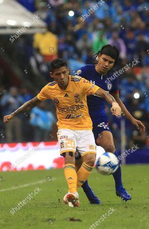 Javier Aquino, Gerardo Floes. Tigres' Javier Aquino, left, fights for the ball with Cruz Azul's Gerardo Floes during a Mexico soccer league match in Mexico City