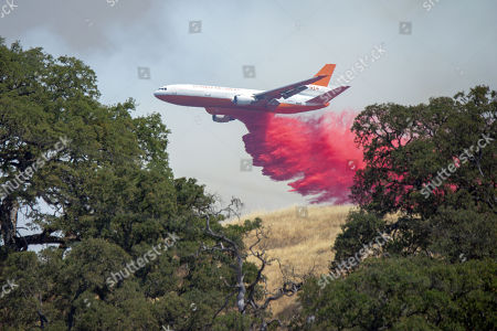 A DC-10 drops retardant on a hill a move the town of Lucerne to stop the spread of the rapidly expanding Ranch Fire Burning in Lake County California