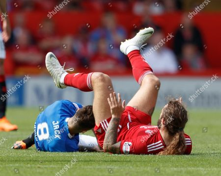 Stevie May of Aberdeen lands on top of Ryan Jack of Rangers after going flying into a challenge for the ball.