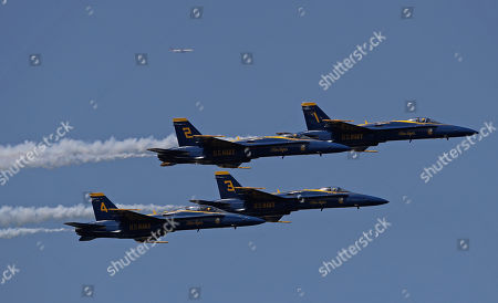 Jimmy Shane, Andrew Tate. Members of the U.S. Navy Blue Angels perform in the Seafair Air Show as a commercial airplane flies by in the distance during Seafair weekend, in Seattle