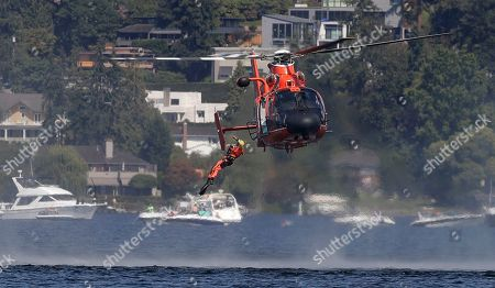 Stock Image of Jimmy Shane, Andrew Tate. A U.S. Coast Guard swimmer jumps from a helicopter during a water rescue demonstration in the Seafair Air Show during Seafair Weekend Festival, in Seattle