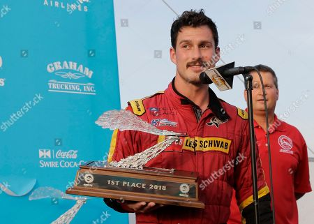 Stock Picture of Jimmy Shane, Andrew Tate. Andrew Tate, driver of the Les Schwab Tires boat, holds his first place trophy after he won the H1 Unlimited Albert Lee Appliance Cup final during Seafair weekend, in Seattle