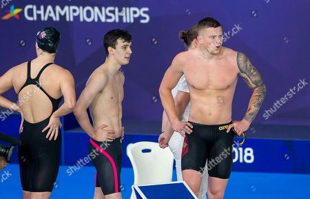 Great Britain's Charlotte Atkinson, Nicholas Pyle and Adam Peaty look on as Freya Anderson brings home a heat victory in the 4 x 100m Medley Relay heats.