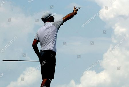 Russell Henley catches a ball on the 12th tee as he practices for the PGA Championship golf tournament, at Bellerive in Saint Louis
