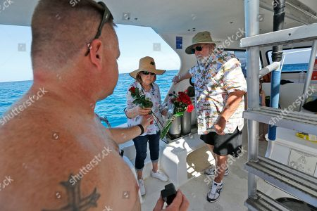 Will Payne, left, Joan Tippy, center, and her husband Craig Tippy, right, prepare to throw flowers into the sea after having deployed a memorial plaque for for Payne's father, Buel Payne and his mother and Joan Tippy's sister, Linda Payne, at the Neptune Memorial Reef near Miami Beach, Fla. The final resting place for Buel and Linda Payne, who spent much of their lives in and around the water, is modeled after the lost city of Atlantis, among lion statues and ornate gates and pillars encrusted with sea life