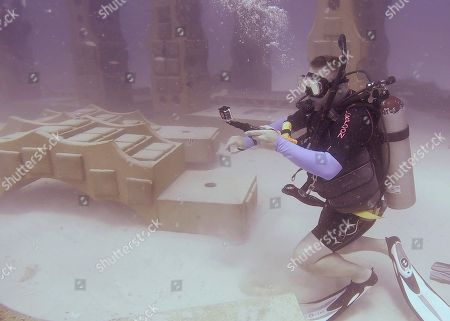 Stock Image of Will Payne, takes a video of a section under construction of the Neptune Memorial Reef after having watched the installation of a memorial plaque for his parents near Miami Beach, Fla. This unusual resting place is exactly what the Paynes say their parents wanted