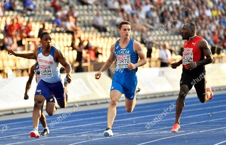 Britain's Chijindu Ujah, Italy's Filippo Tortu and Switzerland's Alex Wilson, from left, cross the line after a men's 100-meter semifinal at the European Athletics Championships in Berlin, Germany