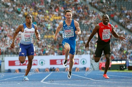 Britain's Chijindu Ujah, left, and Italy's Filippo Tortu, center, compete during a men's 100 meter semi final race at the European Athletics Championships in Berlin, Germany