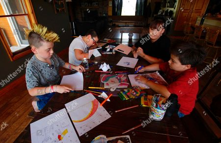 Stock Image of From left, Cash Miller, his sister Kaya Miller, their mother Angie Miller and their brother Jax Miller work on artwork at their kitchen table in Hartford, Wis. Angie Miller bought them some of the hot items in the back to school aisle this year, including glitter glue, scented pencils, special erasable pens, a bullet journal and decorative tape