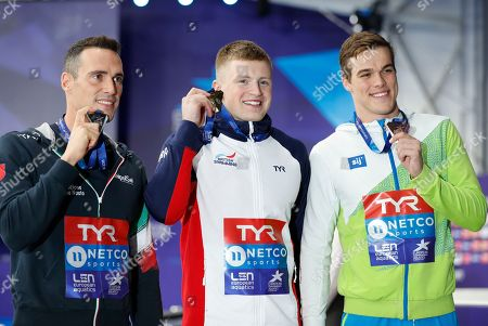Silver medalist Fabio Scozzoli of Italy, left, gold medalist Adam Peaty of Great Britain, bronze medalist Peter John Stevens of Slovenia pose on the podium of the 50 meter breaststroke men final at the European Swimming Championships in Glasgow, Scotland