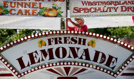 Angel Sanchez hangs a sign on the top of a concession stand during final preparations for the Iowa State Fair, in Des Moines, Iowa. The fair starts Thursday and runs through Aug. 19th