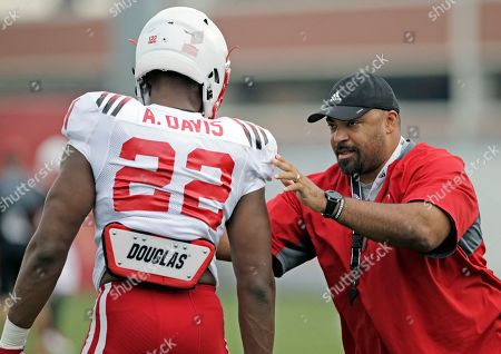 Nebraska offensive line coach Greg Austin works with offensive linebacker Alex Davis (22) during NCAA college football fall practice in Lincoln, Neb