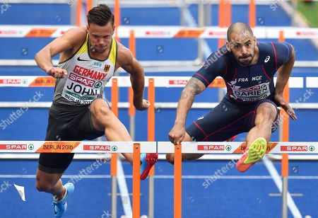 Germany's Alexander John, left, and France's Garfield Darien compete in a men's 110-meter hurdles heat at the European Athletics Championships at the Olympic stadium in Berlin, Germany