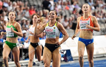 Germany's Pamela Dutkiewicz, center, celebrates after a women's 100-meter hurdles semifinal at the European Athletics Championships at the Olympic stadium in Berlin, Germany