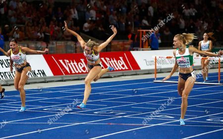 Germany's silver medal winner Pamela Dutkiewicz, Germany's bronze medal winner Cindy Roleder and Belarus' gold medal winner Elvira Herman, from left, cross the line of the women's 100-meter hurdles final at the European Athletics Championships at the Olympic stadium in Berlin, Germany