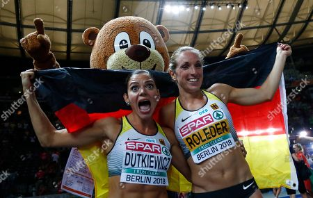 Germany's bronze medal winner Cindy Roleder, right, and silver medal winner Pamela Dutkiewicz, left, celebrate with mascot Berlino after the women's 100-meter hurdles final at the European Athletics Championships at the Olympic stadium in Berlin, Germany