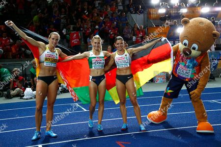 Germany's bronze medal winner Cindy Roleder, Belarus' gold medal winner Elvira Herman and Germany's silver medal winner Pamela Dutkiewicz, from left, celebrate with mascot Berlino after the women's 100-meter hurdles final at the European Athletics Championships at the Olympic stadium in Berlin, Germany